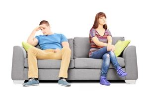 couple sitting on a sofa after criticizing each other