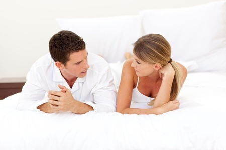 Young couple discussing lying on their bed