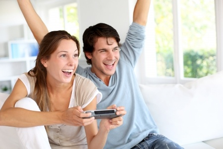 Young couple enjoying video games together at home
