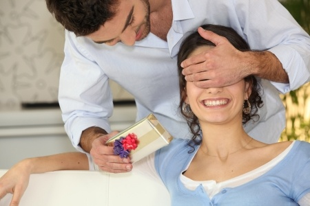 Man surprising woman with gift - occasional gifts to strengthen your marriage
